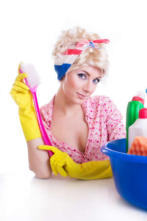 Pinup girl with cleaning brush and set at table over white photo