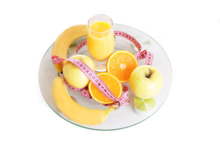 Some fruits, juice and measure tape on scales over white photo