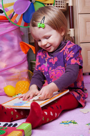 Little girl in playing room with puzzle photo