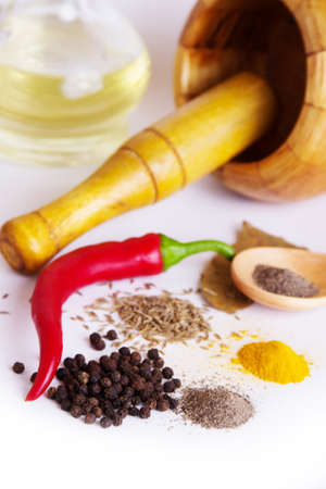 Mortar with pestle, variety of spices and oil over white photo