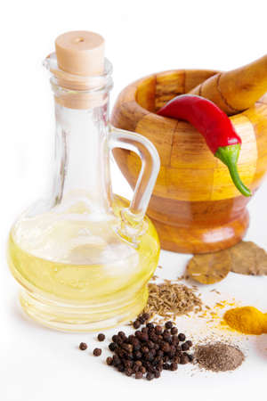 Mortar with pestle, variety of spices and oil over white Stock Photo - 13727986