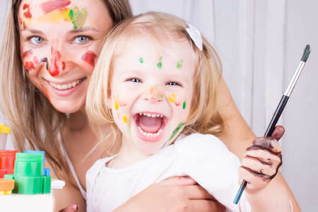 Happy mother and daughter with paint on faces Stock Photo