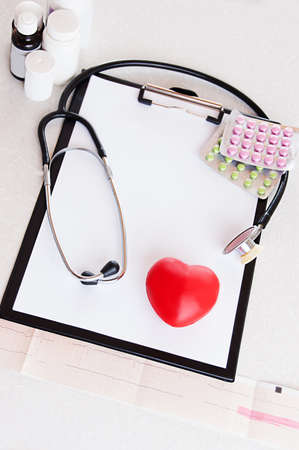 Stethoscope, pills on ecg with heart, medical check concept photo