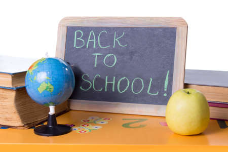 Back to school word on board, books and globe on student table photo