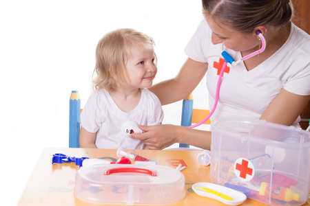 Mother and daughter playing doctor with stethoscope over white photo