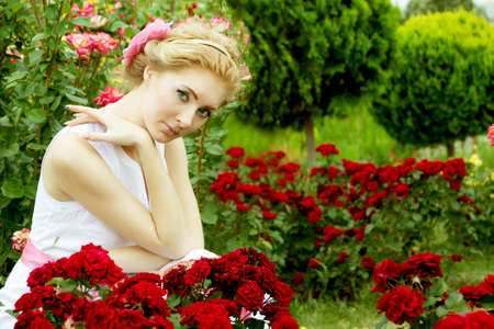 Romantic woman in white dress among rose garden Stock Photo - 14806591