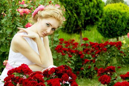 Romantic woman in white dress among rose garden Stock Photo - 14806591