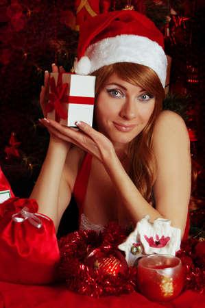 Woman santa helper with present under Christmas tree Stock Photo - 15042509