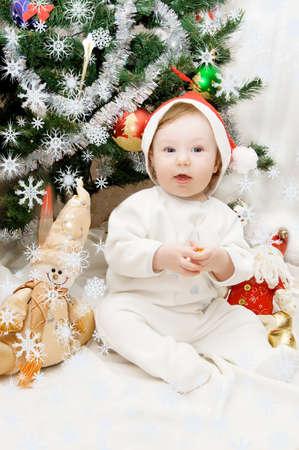 Baby in santa hat sitting under Christmas tree Stock Photo - 15070423
