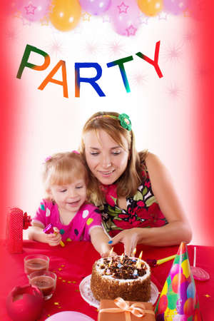 Happy mother with her baby girl celebrating birthday with candles photo