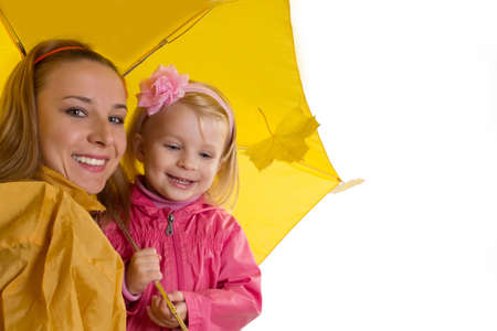 Mother and baby daughter under yellow umbrella on white photo