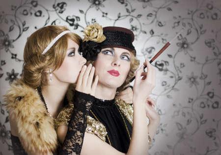 whisper: Two retro styled women sharing secrets on glamourous background Stock Photo
