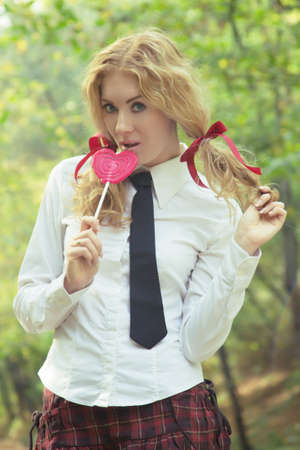 Attractive schoolgirl in tie with lollipop photo