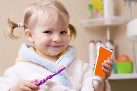 歯ブラシと浴室で管を持つ少女の笑顔