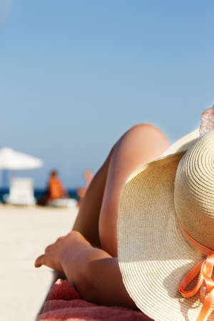 Woman in hat and bikini lying on sandy beach photo
