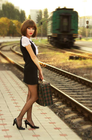 Retro-styled woman with suitcase on the platform waiting for train Stock Photo - 16762466