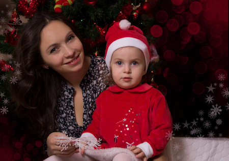 Mother and baby girl in Santa suit near Christmas tree Stock Photo - 16972291