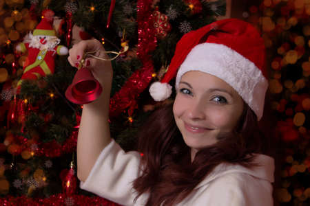 Smiling woman in Santa hat with bell near Christmas Tree Stock Photo - 16972293