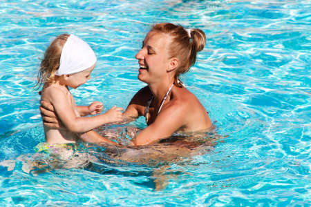 Happy kid playing with mother in swimming pool at summer vacations photo