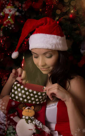Woman Santa helper looking inside Christmas sock Stock Photo - 17015664