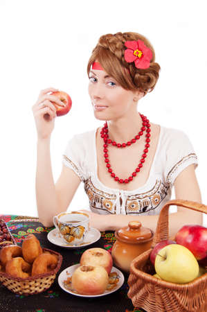 Russian woman eating apples at table over white photo