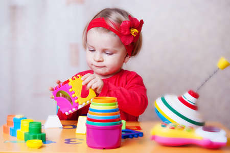 interested baby: Interested baby girl playing sorter in nursery Stock Photo