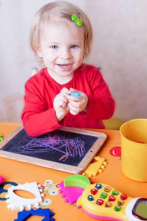 Smiling baby girl drawing with chalk on blackboard in nursery photo
