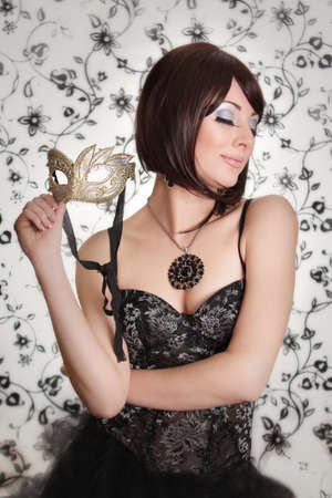 Glamourous retro brunette with mask and corset photo