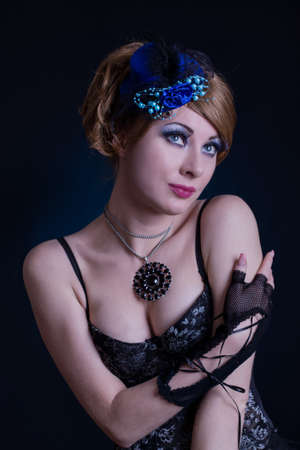 Retro-styled woman in cabaret outfit over dark back photo