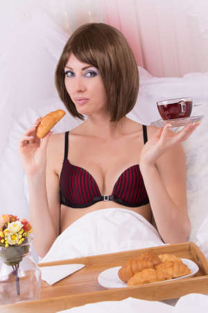 Brunette sensual woman in lingerie with cup of tea in bed Stock Photo - 18766188