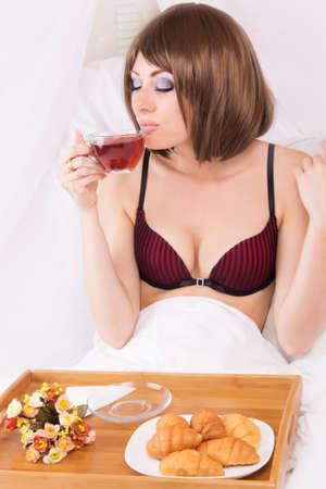 Sensual brunette enjoying morning cup of tea in bed photo
