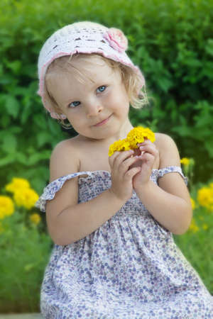 coquettish: Coquettish little girl portrait with yellow flowers Stock Photo