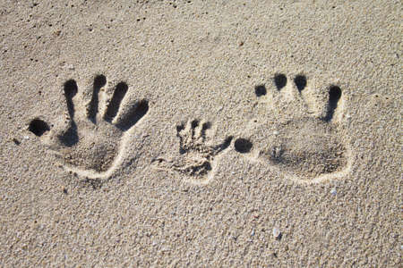 footprints in the sand: Three palm imprints of family on sand