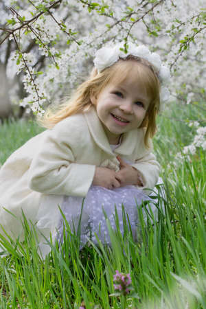 Happy smiling girl sitting among spring blossom garden photo