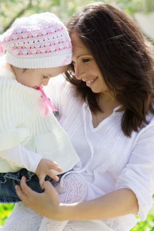 Happy mother and baby girl in spring garden photo