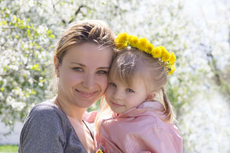 Happy mothre and baby girl in spring garden with dandelion wreath photo