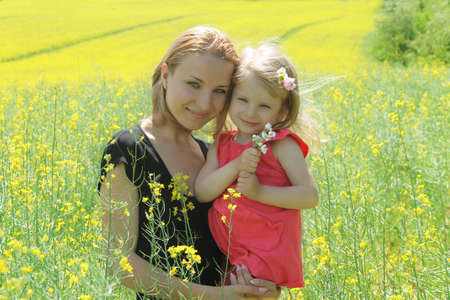 Happy mother and daughter in rapeseed field photo