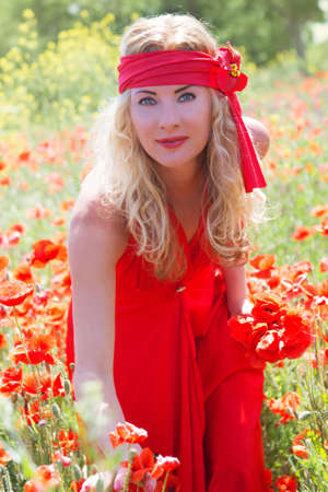 Beautiful woman in long red dress among poppy field photo