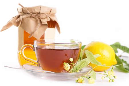 limetree: Lemon tea with linden honey jar and flowers over white
