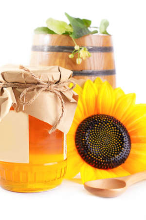 Jar and barrel with honey and flowers isolated on white photo
