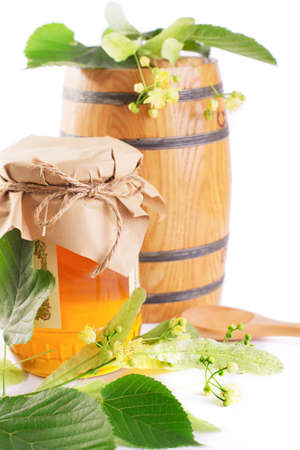 Linden honey jar and barrel with flowers isolated on white photo