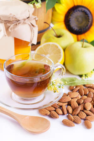 Cup of tea with linden honey, apples, almonds isolated on white photo