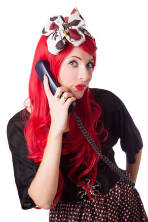Chocked retro woman with red hair on the phone isolated on white photo