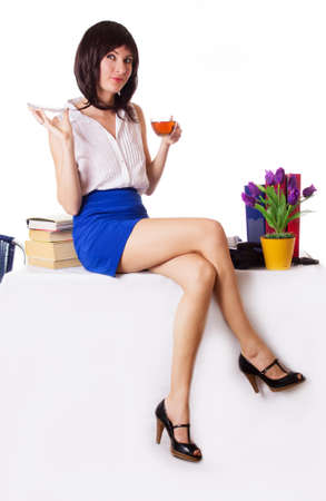 Attractive businesswoman having tea break sitting on table over white photo