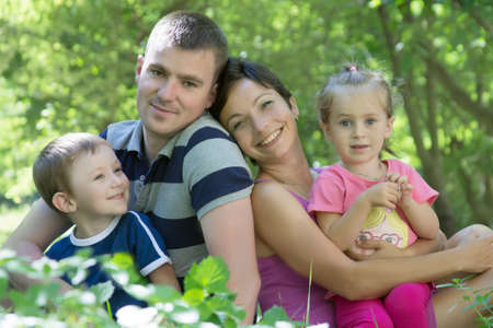 Happy family with two children sitting in the grass photo