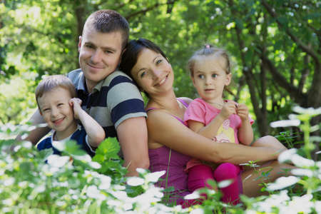 Happy family with two children sitting in park photo
