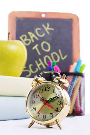 Back to school supplies with clock isolated on white photo