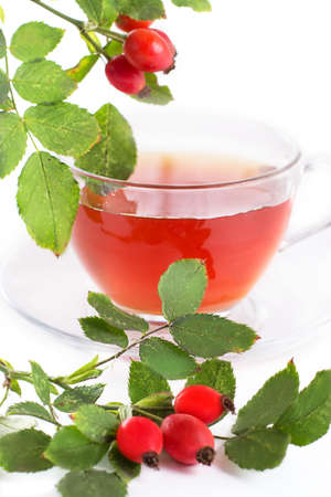 Cup of rose hip tea and berries over white photo