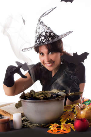 Smiling witch making magic on Halloween isolated over white photo