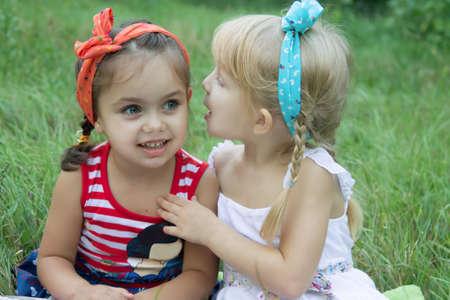 Two girls sharing secrets among grass
